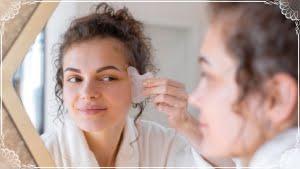 鏡の前でカッサプレートを使ってフェイスマッサージをする女性